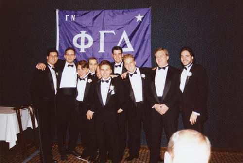 New Adelpi University brothers posing in front of chapter flag at chartering banquet.