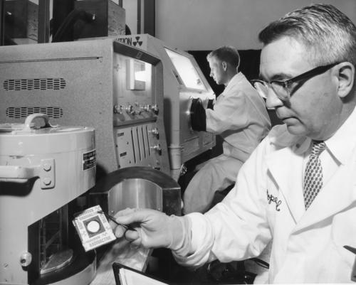 "Milton J. Diamond  (right), Central Foundry Division, inserts a radioactive counting sample in a lead shield ""pig,"" while Robert A. Bailey, GMC Truck&Coach Division, handles radioactive materials in a Berkeley box with its built-in rubber gloves and sleeves. Both trainees are working on laboratory assignments. Between the ""pig"" and the box isa counting instrument, standard equipment in radioisotope laboratories. (X-26878-6)"