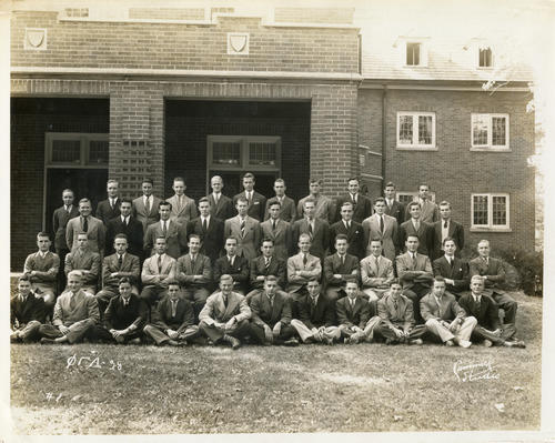 Group picture of the Lambda Chapter at DePauw University in 1938.  Chapter members are seated and standing in front of the chapter house.