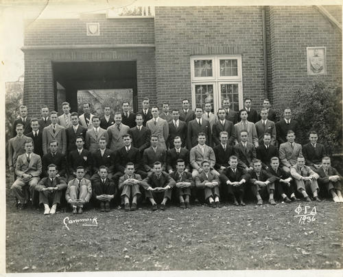 Group picture of the Lambda Chapter at DePauw University in 1936.  Chapter members are seated and standing in front of the chapter house.