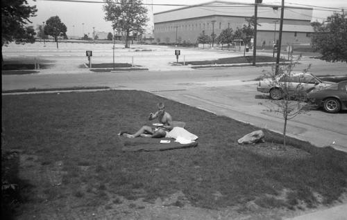 "Man sitting in chapter house yard on blanket - Akron's ""Traditions of Excellence"" during Summer 1989."