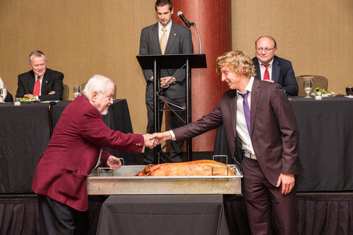 "Brother Kaleb Toweson (IUPUI 2019), shaking hands with Brother Herb Miller (Indiana University 1957), after taking a bite out of the pig, per IUPUI tradition. , The colony which became Iota Pi was established in October 2013.  The charter was presented on April 2, 2016.  There were 39 men pledged and 38 men initiated over the weekend.  A few eligible colony members could not attend the ceremonies and were pledged and initiated at a later date.  Pledging took place on April 1, 2016 in the IUPUI Campus Center in room 405.  Initiation was held at the University Club in downtown Indianapolis.  The Installation Banquet was held at the Hyatt Regency Hotel.  The initiation ceremonies and the Installation Banquet were held on April 2, 2106.  A Pig Dinner was held during the banquet.  Guests included dates, graduate brothers and parents.  George A. ""Skip"" Buckley (Wittenberg University 1980) was keynote speaker.  Others in attendance included:  Colony/Chapter President: Greg Zimmerman (IUPUI 2017) Section Chief: Shawn Meier (Ball State University 2009)  Ritual Team:  Ritualist: Ed Gabe (Hanover College 1990)  President:	Jason Conn (Ball State University 2017) Treasurer:	Ben Willadsen (Ball State 2017) Recording Secretary:	Alejandro Aguiña (DePaul 2016) Corresponding Secretary: Ben Harsha (DePauw 2015) Historian: Daylon Weddle (DePauw 2017) 				 Directors: 			 Andrew Jewell (ISU 2016) Jacob Whitacre (Rose Hulman 2017) Trevor Martin (Indiana State 2017) Jason Waldenmeyer (Rose Hulman 2016)  Legate: Joe Weist (Rose Hulman Institute of Technology 1987, University of Evansville 2000)  Archons / Appointed General Officers / dignitaries in attendance:  William R. Miller (Indiana University 1962, Purdue University 1996) – Former Archon President George A. ""Skip"" Buckley (Wittenberg University 1980) – Former Archon Secretary Kitrick Russell (William Jewell College 2017) – Undergraduate Archon Councilor  Headquarters staff attending:  Duke Murphy (Coastal Carolina University 2011) — Director of Chapter Development Rob Caudill (University of Akron 2004) –Director of Graduate Development Josh Cox (Indiana State 2014) – Field Secretary"