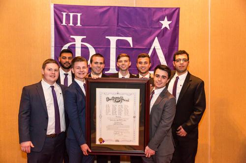 "Iota Pi Alpha Class with Charter and Flag - (Back) Victor Haro (IUPUI 2017) Dillon Wagner (IUPUI 2017) Liam Foreman (IUPUI 2017) Alex Crump (IUPUI 2017) and Mark Botros (IUPUI 2017).  (Front) Adam Price (IUPUI 2017) John Faulkner (IUPUI 2016) and Levi Brown (IUPUI 2017) , The colony which became Iota Pi was established in October 2013.  The charter was presented on April 2, 2016.  There were 39 men pledged and 38 men initiated over the weekend.  A few eligible colony members could not attend the ceremonies and were pledged and initiated at a later date.  Pledging took place on April 1, 2016 in the IUPUI Campus Center in room 405.  Initiation was held at the University Club in downtown Indianapolis.  The Installation Banquet was held at the Hyatt Regency Hotel.  The initiation ceremonies and the Installation Banquet were held on April 2, 2106.  A Pig Dinner was held during the banquet.  Guests included dates, graduate brothers and parents.  George A. ""Skip"" Buckley (Wittenberg University 1980) was keynote speaker.  Others in attendance included:  Colony/Chapter President: Greg Zimmerman (IUPUI 2017) Section Chief: Shawn Meier (Ball State University 2009)  Ritual Team:  Ritualist: Ed Gabe (Hanover College 1990)  President:	Jason Conn (Ball State University 2017) Treasurer:	Ben Willadsen (Ball State 2017) Recording Secretary:	Alejandro Aguiña (DePaul 2016) Corresponding Secretary: Ben Harsha (DePauw 2015) Historian: Daylon Weddle (DePauw 2017) 				 Directors: 			 Andrew Jewell (ISU 2016) Jacob Whitacre (Rose Hulman 2017) Trevor Martin (Indiana State 2017) Jason Waldenmeyer (Rose Hulman 2016)  Legate: Joe Weist (Rose Hulman Institute of Technology 1987, University of Evansville 2000)  Archons / Appointed General Officers / dignitaries in attendance:  William R. Miller (Indiana University 1962, Purdue University 1996) – Former Archon President George A. ""Skip"" Buckley (Wittenberg University 1980) – Former Archon Secretary Kitrick Russell (William Jewell College 2017) – Undergraduate Archon Councilor  Headquarters staff attending:  Duke Murphy (Coastal Carolina University 2011) — Director of Chapter Development Rob Caudill (University of Akron 2004) –Director of Graduate Development Josh Cox (Indiana State 2014) – Field Secretary"