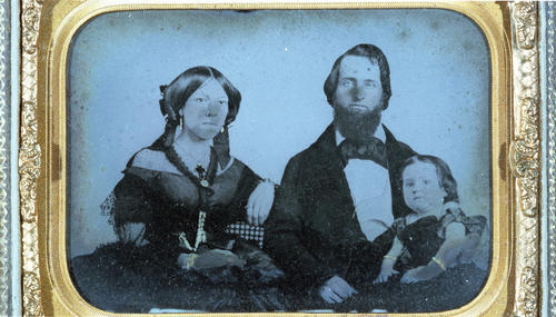 "John Templeton McCarty (Jefferson College 1848) and his family.  Taken in 1860 just prior to his death.  The original image is a daguerreotype. , John Templeton McCarty (1828-1860)  	 ""Mac"" or ""Johnty,"" as he was called by his brothers, was born in Brookville, Indiana, to Scotch-Irish parents on August 28, 1828. His father was wealthy, making his money from merchandising, large-scale farming, pork packing, selling real estate and operating stage-coach and canal-boat lines. In addition, he was a prominent Mason and member of the state legislature. John's mother was a cousin of statesman John C. Calhoun.  McCarty was educated in the public schools, studied Greek and Latin under a local clergyman and at seventeen went to Oxford, Ohio to enter Miami University. There he remained for two years, pursuing only a ""partial course,"" before matriculating to Jefferson College in 1846. At Jefferson, he soon determined to establish a new organization, whose emblem is now so proudly borne by so many.  McCarty the student is described as a young man of unusually fine physique, open-hearted, generous, genial, sociable, and very popular. He was a clear thinker, a vigorous writer, a forcible speaker with a ready wit; his frank Western manner and joyous laughter made him loved by all. At the same time, he was a born adventurer and fighter, as his later life disclosed.  Immediately after his graduation, he returned to Brookville to take up the study and practice of law. Being, however, of a high-spirited and adventurous nature, he soon organized a company with himself as captain and set out in the spring of 1849 across the plains with the ""Forty-niners"" to search for gold in California. The diary which ""Mac"" kept of this perilous journey is historically valuable and extremely interesting for its descriptions of the country through which the wagon caravan trekked and for its accounts of buffalo hunts, of Indian troubles, of cholera epidemics, of hunger, thirst, privation, and death. By virtue of both vested authority and natural ability, ""Mac"" was the leader of that expedition across the continent. It was he who blazed the most difficult trails, first swam the rivers, killed the first game and dug the first gold. It was he, too, who had all the dealings with the native Americans, in one instance overpowering a hostile Indian in hand-to-hand combat.  To us, the most amazing and inspiring incident of the entire journey was a chance meeting between McCarty and another member of Phi Gamma Delta, Bolivar G. Krepps (Washington '49), each independently seeking his Eldorado in the gold rush, on the banks of the Sweetwater River on the evening of June 7th, 1849. Neither had ever seen the other before, yet they met in the midst of the trackless west at a time when the entire roll of the ""Delta Association"" numbered not more than twenty-five. McCarty's diary tells of the splendid feast with which they celebrated and of the many hours of fellowship and conversation which followed. Before parting, they stood beside that limpid stream and, with uncovered heads, 'neath the brilliant stars, drank a solemn toast to the prosperity of the ""Delta Association"" and to all brothers who should live after them.  Upon arrival at the gold fields, the adventurous group of ""Forty-niners"" fared none too well and the company shortly disbanded. McCarty we nt to San Jose, the seat of the first California government, where he became clerk of the first legislature. In February, 1850, he moved to Marysville, California, to practice law, and was twice elected county recorder and criminal court judge. In 1853, he met Mary E. Pierson, becoming so interested in her that when she went East to school the next year he followed her. While crossing the Isthmus of Panama on the way to New York, he contracted the ""Panama Fever"" which undermined his health and led to his death six years later. Nevertheless, he and Mary were married in 1854 and after an extensive Eastern honeymoon, returned via Brookville and New Orleans to McCarty's new house in Marysville. Their one daughter was born, whose presence was the highlight of the Portland Ekklesia of 1938.  Up to 1860, John T. had been a man of considerable wealth, but through the misfortune of a man whose bond he had signed, he then found himself suddenly in difficulties. On the advice of friends he resolved to recoup his fortunes in the Nevada mines and sold all of his property preparatory to moving. Just before his scheduled departure, he was stricken ill. He died February 4, 1860. He was buried in the cemetery at Marysville, where his resting place was marked by the Fraternity with a handsome stone fittingly inscribed: "". . . erected to his memory by the College Fraternity of Phi Gamma Delta of which he was a founder and the influence of which, magnified beyond his fondest hopes, lives to ennoble his memory."" In 1932 his remains and the stone were removed by the Fraternity to the Sierra View Memorial Park in the same city.  McCarty's Gravesite  McCarty died on February 4, 1860, and was buried in the pioneer cemetery in Marysville. The grave was unmarked until William F. Chamberlin (Denison 1893) arranged for a stone to be placed here.  In 1932 the Fraternity moved McCarty's remains to another nearby cemetery. Hence, the directions provided in The History of Phi Gamma Delta, Tomos Alpha are incorrect.  Directions  Drive north from Sacramento on State Route 70 for around forty miles until you are five miles south of Marysville. As the highway becomes four-lane, you will see a McGowan parkway off-ramp. Take that exit and turn east at the stop sign; proceed to Olive Avenue, turn left, and continue north, which will bring you to the gates of Sierra View Memorial Park. McCarty's gravesite is located at the extreme back part of the cemetery on the left side of the mausoleum towards the equipment garage, under a large tree. It is on Lot C, Section 40, Block 6."