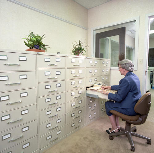 New International Headquarters Building and Staff in July 1985. The building was dedicated on May 18, 1985.  Female staff member looking through files.