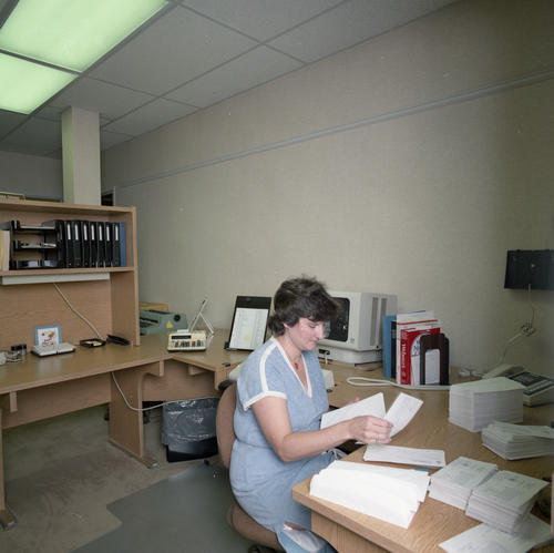 New International Headquarters Building and Staff in July 1985. The building was dedicated on May 18, 1985.  Female staff member at desk.