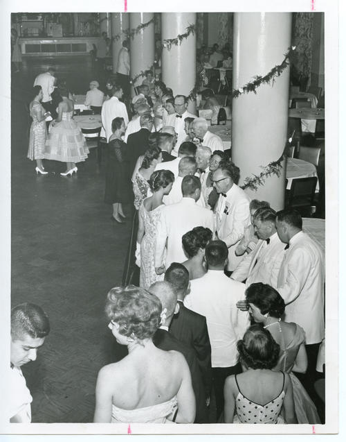 "The FIJIs and their sweethearts greet ""Scoop"", Mrs. Wilkinson, and the Archons (Front). The 112th Ekklesia was held in Washington, DC at the Shoreham Hotel, on August 24-27, 1960. There were 605 Brothers registered for the 112th Ekklesia."