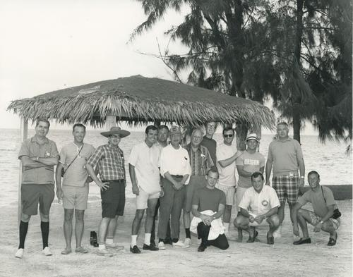 Group of field secretaries on beach under canopy with Bill Zerman (University of Michigan 1949).  Picture taken in August 1968 at the 120th Ekklesia in the Bahamas.