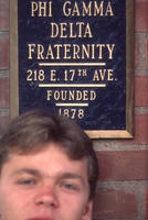 Brother in front of Ohio State Chapter House plaque