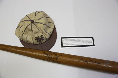 "Christy Mathewson, Sr. (Bucknell University 1902) Baseball Cap and baseball bat.  Cap was worn during Mathewson's career.  He was arguably the greatest FIJI baseball player ever and in the 17 years he pitched for the New York Giants, he had a winning percentage of 0.665 in 634 games.  One of his outstanding achievements was in the World Series of 1905 against the Philadelphia Athletics when he pitched three shut-out games within five days. , From http://baseballhall.org/hof/mathewson-christy  He was the first great pitching star of the modern era, and is still the standard by which greatness is measured.  Christy Mathewson changed the way people perceived baseball players by his actions on and off the field. His combination of power and poise – his tenacity and temperance – remains baseball's ideal.  Born Aug. 12, 1880 in Factoryville, Pa., Mathewson attended Bucknell University and played on the school's baseball and football teams. He signed his first pro baseball contract in 1899 – a rarity for a college-educated player in that era – and in 1900 went from the New York Giants to the Cincinnati Reds and back to the Giants in a round of deals that included a trade for future Hall of Fame pitcher Amos Rusie.  Using his famous ""fadeaway"" pitch – what today would be called a screwball – the 6-foot-1, 185-pound right-hander baffled batters with pinpoint control. He won 20 games in his first full big league season in 1901, posted at least 30 wins a season from 1903-05 and led the National League in strikeouts five times between 1903 and 1908.  He set a modern era record for wins by an NL pitcher with 37 in 1908, a year when he completed 34 of his 44 starts en route to more than 390 innings pitched.  In the postseason, Mathewson pitched three shutouts in three starts in the 1905 World Series.  ""He could pitch into a tin cup,"" said Hall of Fame second baseman Johnny Evers.  From 1903-14, Mathewson never won fewer than 23 games in a season and led the NL in ERA five times.  As his career wound down, Mathewson was traded back to the Reds in 1916, finishing his career on Sept. 4 of that year in a matchup against longtime rival Three Finger Brown. In 17 seasons, Mathewson finished with 373 wins against just 188 losses – a figure that leaves him tied with Grover Cleveland Alexander for the most wins in NL history and third-most all-time.  In 1918, Mathewson enlisted in the Army during World War I. While serving as a captain in France, he was accidentally gassed during a training exercise. He spent the next seven years battling tuberculosis and died on Oct. 7, 1925.  He was one of the first five players elected to the Hall of Fame in 1936.  ""He had knowledge, judgment, perfect control and form,"" said Hall of Fame manager Connie Mack of Mathewson. ""It was wonderful to watch him pitch – when he wasn't pitching against you."""